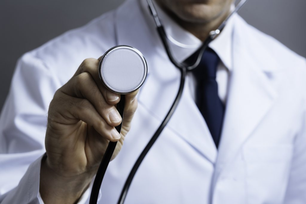 My equipment. Close up of smart concentrated professional doctors hands holding stethoscope and using it while posing on a grey background.