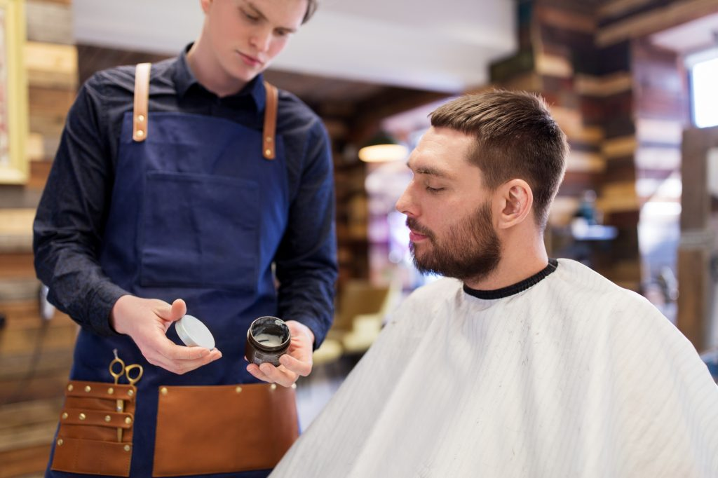 grooming, hairdressing and people concept - hairstylist showing hair styling wax to male customer at barbershop
