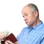 dissatisfied senior bald man is examining his cash savings